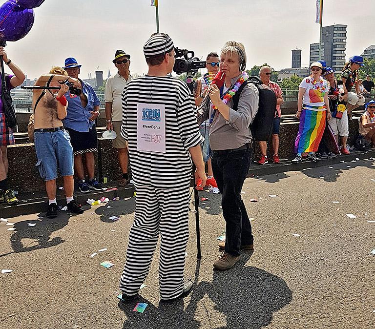 """Frank Überall, DJV-Bundesvorsitzender und KJV-Mitglied, gibt ein Interview. Mit dem Sträflingskostüm und den Aufschriften """"#FreeDeniz"""" und """"Journalismus ist kein Verbrechen"""" sorgt er für Aufsehen. Foto: Corinna Blümel"""