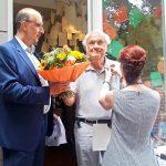 Gert Lahmann (Mitte) ist dem DJV vor 60 Jahren beigetreten. Er hat unter anderem für BILD und BILD am Sonntag gearbeitet. Der Landesvorsitzende Frank Stach überreicht Blumen, Pressereferentin Sascha Fobbe steckt die Nadel an den Kragen. Foto: Carmen Molitor