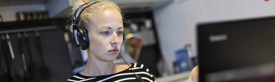 Eine junge Frau arbeitet mit Laptop in der Küche.