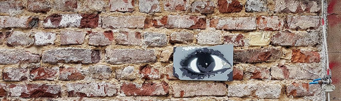 Grafittibild eines Auges auf einer Ziegelwand.