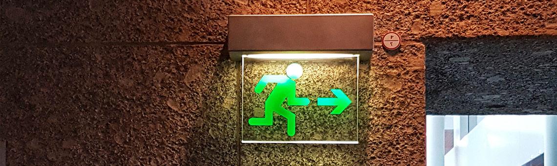 Symbolbild. Beleuchteter Hinweis auf einen Notausgang.