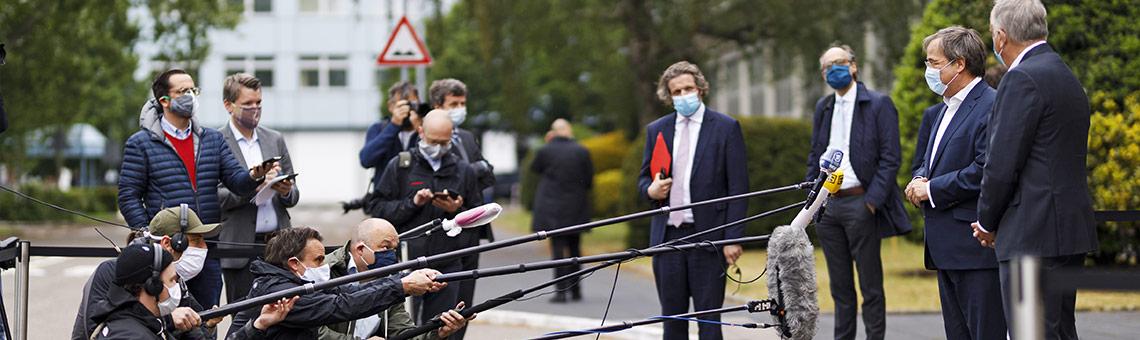 Medienvertreter mit Schutzmasken und auf Abstand zu NRW-Ministerpräsident Armin Laschet beim Pressetermin im Ford-Werk zur Wiederaufnahme der Produktion Anfang Mai.