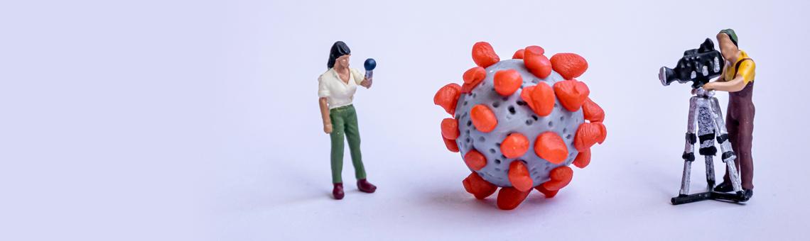 Symbolbild. Kleine Spielfiguren als Kamerateam und ein Virus-Modell