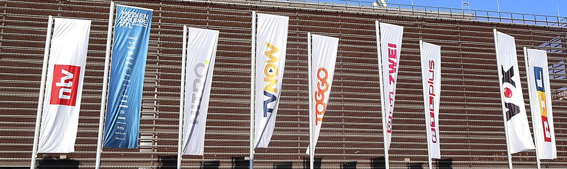 Fahnen der Sender und Plattformen am Unternehmenssitz der Mediengruppe RTL Deutschland in Köln-Deutz. | Foto: Corinna Bl+ümel